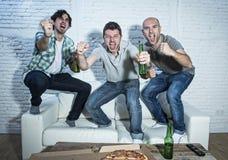 Fanatische Fußballfane der Freunde, die Spiel im Fernsehen feiert schreiendes verrücktes glückliches des Ziels aufpassen Stockbilder