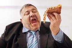 Fanatisk sjukligt fet man som biter en skiva av pizza Arkivfoto