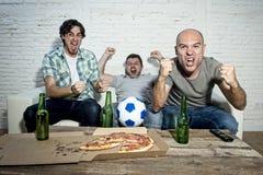 Fanatiska fotbollsfan för vänner som håller ögonen på leken på tv som firar målet som skriker galet lyckligt Royaltyfria Bilder