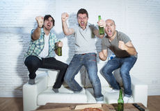 Fanatiska fotbollsfan för vänner som håller ögonen på leken på tv som firar målet som skriker galet lyckligt Royaltyfria Foton