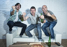 Fanatiska fotbollsfan för vänner som håller ögonen på leken på tv som firar målet som skriker galet lyckligt Arkivbilder