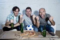 Fanatiska fotbollsfan för vänner som håller ögonen på leken på tv som firar målet som skriker galet lyckligt arkivbild