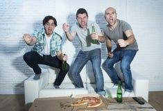 Fanatiska fotbollsfan för vänner som håller ögonen på leken på tv som firar målet som skriker galet lyckligt Fotografering för Bildbyråer