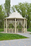 Fancy arbor in a park. Beautiful gazebo in spring park surrounded by trees and green grass Royalty Free Stock Image
