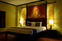 Fancy Asian style bedroom. A comfortable Thai bedroom decorated and furnished in ornate Asian style Royalty Free Stock Photos