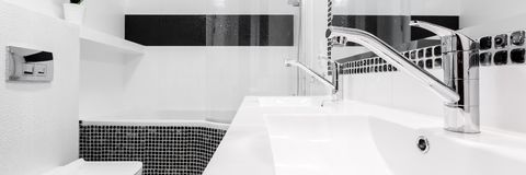 Bathroom with two sinks, panorama. Stylish bathroom with two sinks, black and white small tiles, panorama stock photography