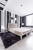 Fancy bed in room. Fancy bed with tufted velvet headboard in modern room with fur carpet Stock Images