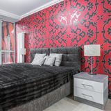 Fancy bedroom with ornament wallpaper. Fancy bedroom with double bed, nightstand, window, black and red ornament wallpaper stock photography