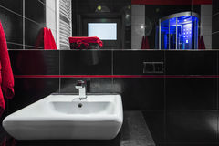 Fancy black bathroom idea. Modern bathroom with black wall tiles, big mirror and white sink royalty free stock photography