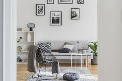 Fancy metal chair with grey blanket next to grey pouf in trendy living room. Fancy black metal chair with grey blanket next to grey pouf in trendy living room royalty free stock images
