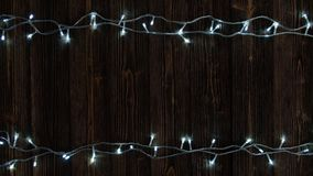 Fancy blinker light bulbs or garlands and wreath on wood table for Christmas or New years decoration background, Christmas colorfu. L glowing lights border stock video footage