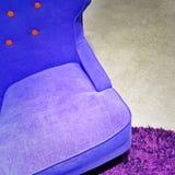 Fancy blue armchair on purple carpet Stock Images