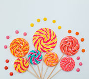 Fancy bouquet of lollipop sweet candy on white background. Colorful print of caramel on sticks. Holiday party concept. Copy space. Lay flat top view Royalty Free Stock Photo