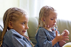Fancy braids sisters. Two young girls wearing dreadlocks, watching TV Royalty Free Stock Photos