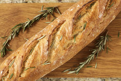Fancy bread with herbs and a cutting board on a granite counter Stock Photos