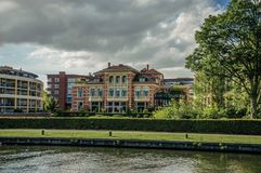 Fancy brick building next to wide tree-lined canal under cloudy sky at sunset in Weesp. Quiet and pleasant village full of canals and green near Amsterdam Royalty Free Stock Photography