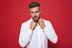 Fancy brunette man 30s with stubble in white shirt looking on ca stock photography