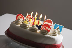 Fancy cake with road signs and burning candles Stock Photo