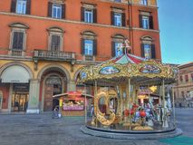 Fancy Carousel Merry Go Round. Fancy and beautiful Carousel / Merry-Go-Round / Kids Playground / Entertainment  in front of an orange building of a square in stock photo
