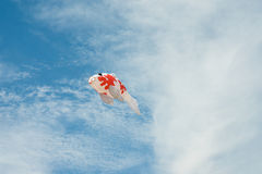 Fancy carp fish shaped kite flying in blue cloudy sky Stock Photo