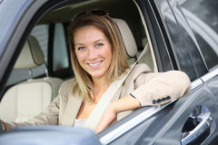 Fancy cheerful woman sitting in brand new car Royalty Free Stock Images