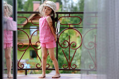 Fancy child girl in sunhat posing on balcony Royalty Free Stock Photography