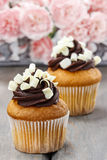 Fancy chocolate cupcakes on wooden table Royalty Free Stock Photos
