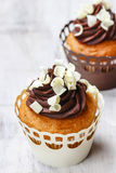 Fancy chocolate cupcakes on wooden table Stock Photos