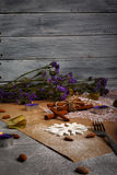 A fancy Christmas composition. Purple flowers, candles, white snowflake, cinnamon, and a fork on a table background. stock photo