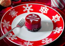 Fancy Christmas pastry on a red plate. A raspberry chocolate fancy Christmas pastry on a red snowflake plate and red charger Royalty Free Stock Photos