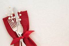 Fancy Christmas Table Place Setting with red napkin, silverware, and white berries on creamy white tablecloth background with copy
