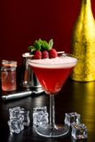 Raspberry martini cosmopolitan cocktail drink. Fancy cocktail alcohol beverage drink fresh mint raspberry vodka gin ice cubes bar restaurant hotel bartender stock photo