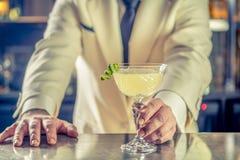 Fancy cocktail drink lime garnish bartender hands. Green apple cocktail alcohol drink lime zest bartender mixologist hands royalty free stock images