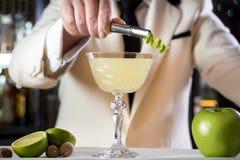Fancy cocktail drink lime garnish bartender hands. Green apple cocktail alcohol drink lime zest bartender mixologist hands royalty free stock photography