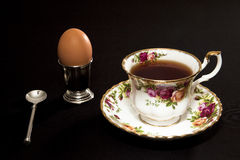 Fancy coffee cup and egg. Breakfast setting of a fancy china coffee cup and saucer with spoon and egg in silver cup isolated against a black background Royalty Free Stock Images