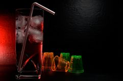 Fancy Colorful Drink in a Highball Glass with Plastic Shooter Glasses in the Background royalty free stock images