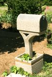 Fancy Country Mailbox. Close-up of a heavy concrete mailbox with plants around it and in the background Stock Photos