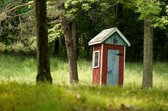 Fancy Country Outhouse. Fancy but rustic red and white country outhouse sits in heavy woods Royalty Free Stock Image