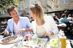 Fancy couple eating in outdoor restaurant Stock Photos