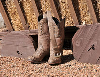 Fancy cowboy boots with belt. A view of fancy, stylish crocodile cowboy boots and a belt in front of a wooden hay wagon Stock Photography
