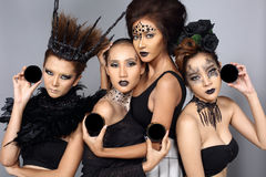 Fancy Creative Talent Make up and Hair style on group of Four As. Ian Beautiful Models, Black jewelry silver glitter eyeshadow, studio lighting gray background royalty free stock photo