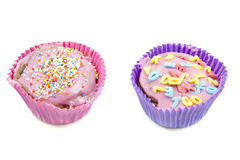 Fancy cup cakes. Two fancy colorful decorated cup cakes isolated over white stock photos