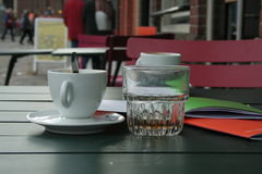Fancy a cup of coffee?. Coffee and a glass of water on a table royalty free stock photos