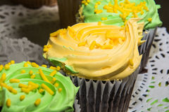 Fancy Cupcakes. Green and yellow frosting with sprinkles on chocolate cupcakes Royalty Free Stock Photography