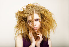 Embarrassment. Shaggy Red-Haired Curly woman grimacing. Play the Ape Royalty Free Stock Photography