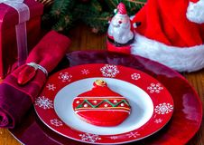 Sugar cookie and fancy dishes for santa. A fancy decorated sugar cookie  rests on a festive holiday plate and charger to make an extra special place setting for Stock Photography