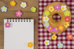 Fancy Doughnuts. Top view of a fancy donut on wooden table with opened notepad Royalty Free Stock Photos