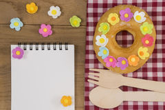 Fancy Doughnuts. Top view of a fancy donut on wooden table with a spoon, fork and opened notepad Royalty Free Stock Images