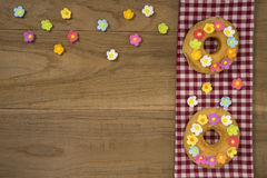 Fancy Doughnuts. Top view of two fancy donuts on wooden table with copy space Royalty Free Stock Photos