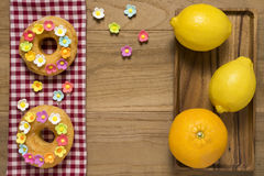 Fancy Doughnuts. Top view of two fancy donuts on wooden table with orange and lemon Royalty Free Stock Photo
